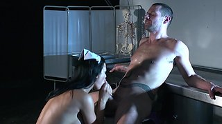 A milf with big fake tits is getting fucked hard in the dark