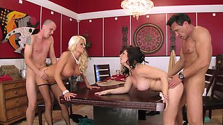 A blonde and a brunette are swapping partners on the wooden table