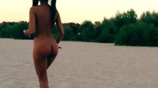 Nude Innuska playing frisbee on the beach