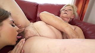 Old and young woman are making some sexy lesbian love on the sofa